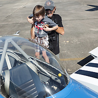 Randall Millis lifts his grandson Connor Millis, 6, to look in the cockpit of a stunt plane during Aviation Day Saturday October 11, 2014 at Wilmington International Airport in Wilmington, N.C. (Jason A. Frizzelle)