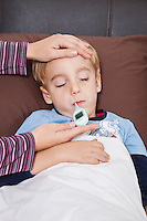 Mother checking unwell little boy's temperature with thermometer