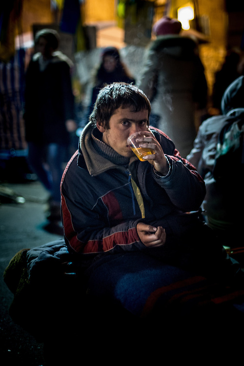 A young man rests and drinks hot tea on the Independance Square, at night.