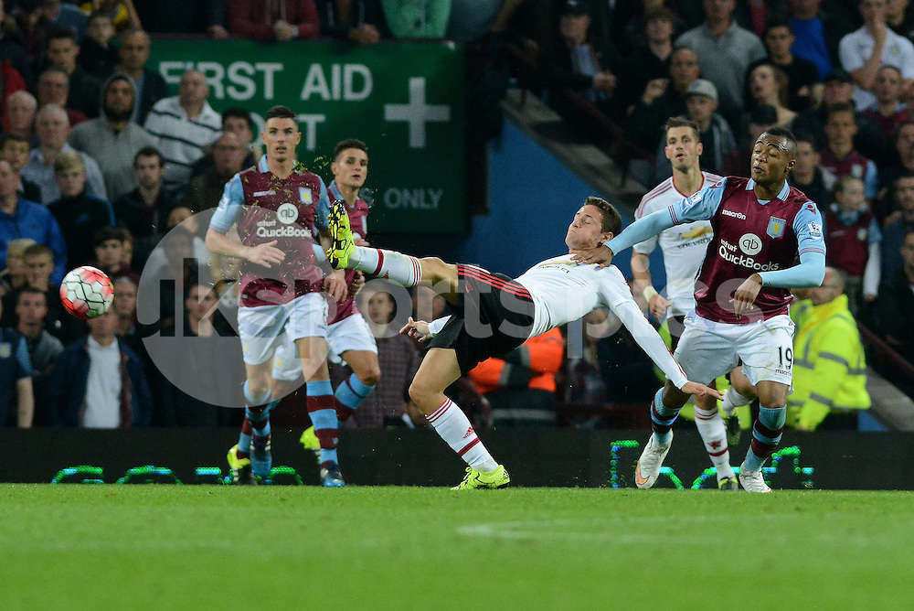 Manchester United's Ander Herrera tries to get a long range shot on goal pressured by Aston Villa's Jordan Ayew during the Barclays Premier League match between Aston Villa and Manchester United at Villa Park, Birmingham, England on 14 August 2015. Photo by Garry Griffiths.