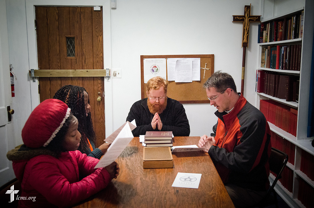 The Rev. Roy Axel Coats (center) leads a group in prayer during a youth confirmation study session Thursday, March 27, 2014, at Lutheran Church of the Redeemer in Baltimore, Md. Seated are (L-R) Princess Greah, 17, Samantha Nah, 16, and the Rev. Steven Schave, director of LCMS Urban & Inner-City Ministry. LCMS Communications/Erik M. Lunsford