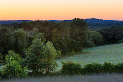 Fields and trees at dusk on Sagamore Hill in Hamilton, Massachusetts.