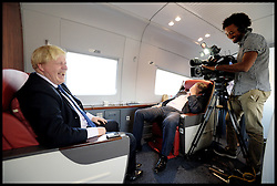 The London Mayor Boris Johnson with BBC London Political Editor Tim Donovan laughing as they try and do an interview but keep being interrupted by announcements on the train as they take the train from Beijing to Shanghai on Day 4 of his Trade Mission to China, Wednesday, 16th October 2013. Picture by Andrew Parsons / i-Images