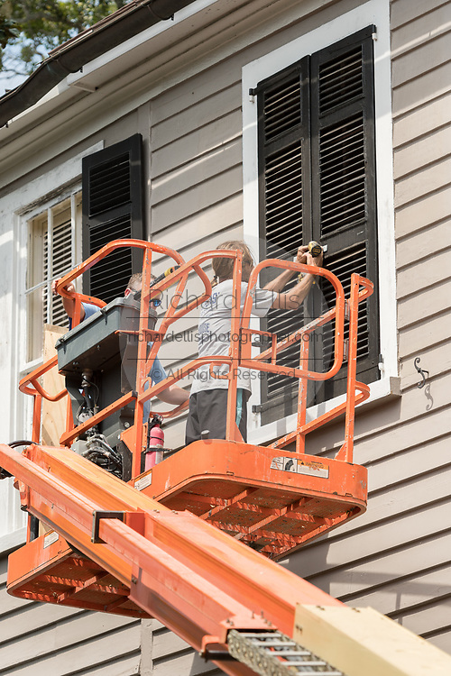 Workers secure hurricane shutters on a historic home in preparation for Hurricane Irma September 8, 2017 in Charleston, South Carolina. Imra is expected to spare the Charleston area but hurricane preparations continue as Irma leaves a path of destruction across the Caribbean.