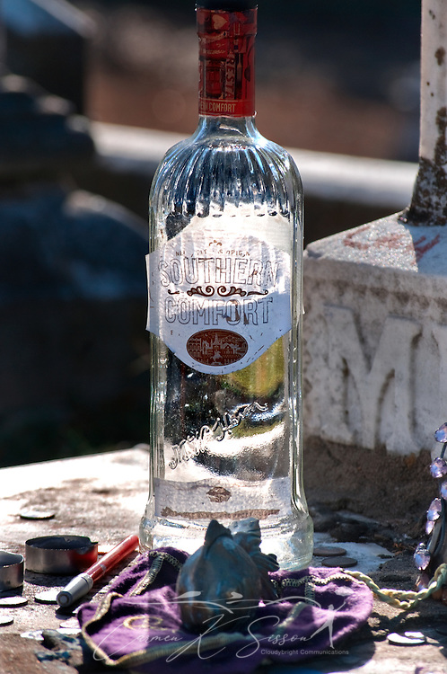 A bottle of Southern Comfort, along with candles and a fish figurine, sits on the grave of gypsy queen Kelly Mitchell at Rose Hill Cemetery in Meridian, Mississippi. Mitchell was a member of the Gypsy Royal Family, many of whom are buried nearby. Tourists and visitors often leave gifts of fruit, trinkets, and liquor on the family's graves. (Photo by Carmen K. Sisson/Cloudybright)