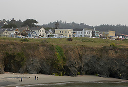 People walk along the beach amongst the cliffs with the town of Mendoicino sitting above, Mendocino, California, USA.