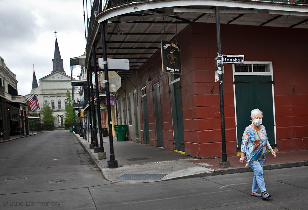 Woman  with a facemask walking in New Orleans on Bourbon street  on  Easter  on Sunday, The State of Louisiana is under a  stay-at-home order called to stop COVID-19.