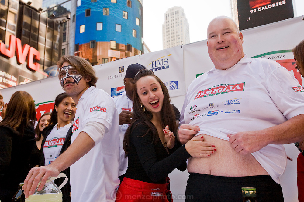A cheerleader pats the stomach and applies olive oil to one of the contestants in the Famous Famiglia world championship pizza eating contest in New York City's Times Square, where Joey Chestnut won the $5,000 first prize by eating 45 slices of cheese pizza in 10 minutes.  (Joey Chestnut is featured in the book What I Eat: Around the World in 80 Diets.)  Each slice weighed 109 grams (3.84 ounces) and contained 260 calories. In ten minutes Joey consumed 10.81 pounds (4.9 kilograms) of pizza and drank a gallon of water. The pizza contained 11,700 calories.