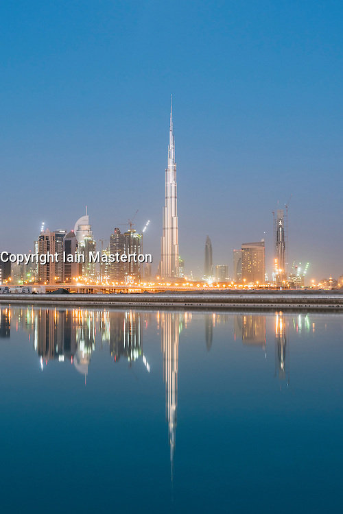 Skyline of skyscrapers and Burj Khalifa tower before sunrise in Dubai United Arab Emirates