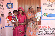 Two young mothers with their babies, pictured outside a brightly painted Anganwadi clinic in a remote part of western Madhya Pradesh, India.