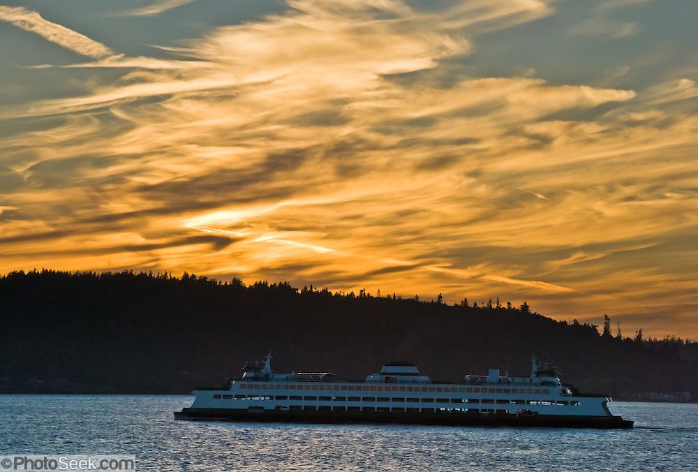 The Spokane, part of the Washington State Ferry system, plies Puget Sound towards sunset over Kingston on the Kitsap Peninsula, Washington.