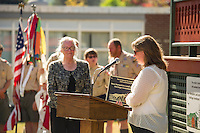 Amy Dixon of the NH Division of Historical Resources presents Belmont Heritage Commission Chairman Linda Frawley with a dedication plaque during the Belmont Bandstand - Community Salute on Sunday afternoon.   (Karen Bobotas/for the Laconia Daily Sun)