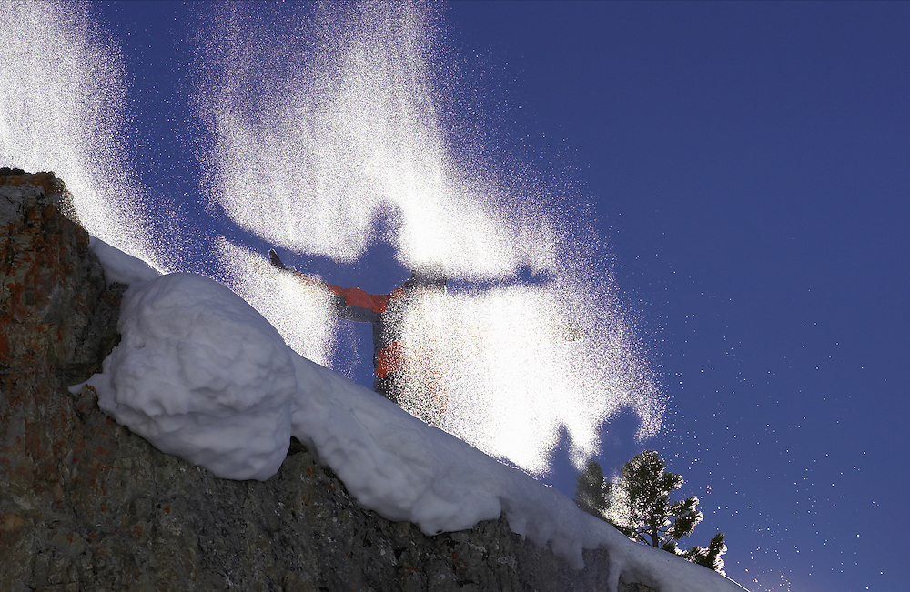 Lifestyle. Silhouette of skier with arms outstretched behind a backlit spray of snow