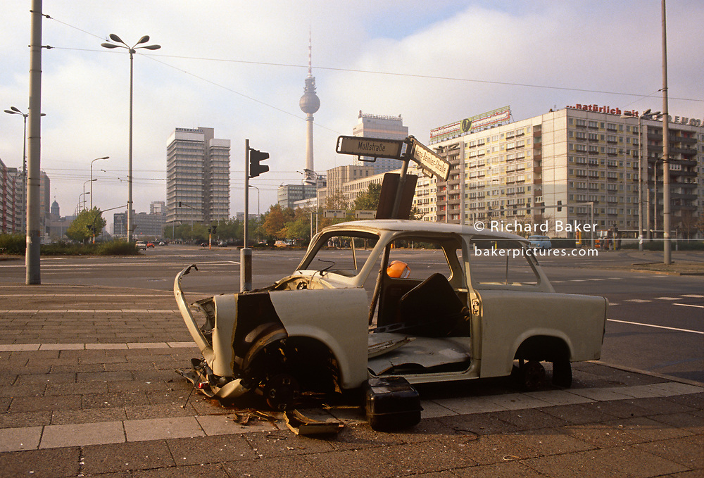 "Six months after the fall of the Berlin Wall, a Trabant car sits wrecked on the corner of Mollstrasse and Hans-Beimler-Strasse in east Berlin (former DDR), on 1st June 1990, in Berlin, Germany. The DDR-produced Trabant suffered poor performance, but its smoky two-stroke engine regarded with affection as a symbol of the more positive sides of East Germany. Many East Germans streamed into West Berlin and West Germany in their Trabants after the opening of the Berlin Wall. It was in production without any significant change for nearly 30 years. The name Trabant means ""fellow traveler"" in German."