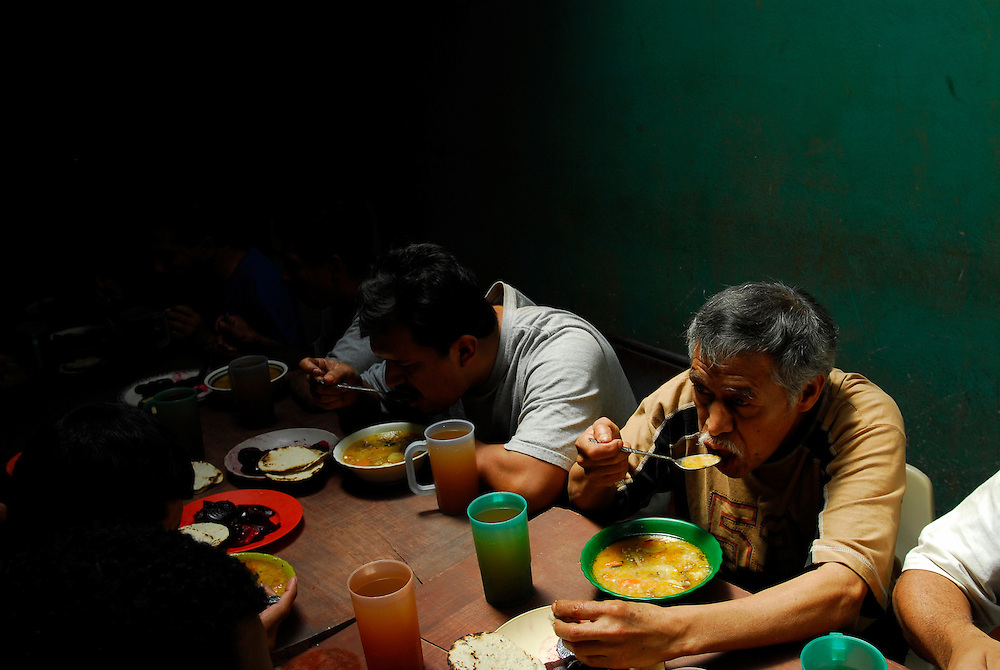 "Ramiro Garcia ""Coyote"" Orenano, 64, right, eats a meal at Casa Hogar, a rehabilitation home for alcohol and drug addicts, outside of Antigua, Guatemala. Coyote had been abusing alcohol nearly his entire life and ""just wanted to finally quit."" He has been a resident of Casa Hogar for 45 days...Casa Hogar currently houses 44 men (with a maximum of 60.) Jorge Rosales, himself a former drug user, founded the home 2 years ago after he kicked his habit and left the garbage dump he had been living in for thirteen months...If accepted into Casa Hogar the voluntary residents must first spend 6 days in a first floor room of mattresses, are denied showers and must eat meals separately from other residents. Patients in the first floor zone suffer from convulsions, vomiting and other withdrawal symptoms and are monitored round the clock by a nurse. Most alcoholics who enter the program have been drinking rubbing alcohol, according to Rosales, because it is so inexpensive...""If they make it"" says resident Byron Rosales, ""they can join us up top."" It is up to the individual when they feel they are ready to leave the home."