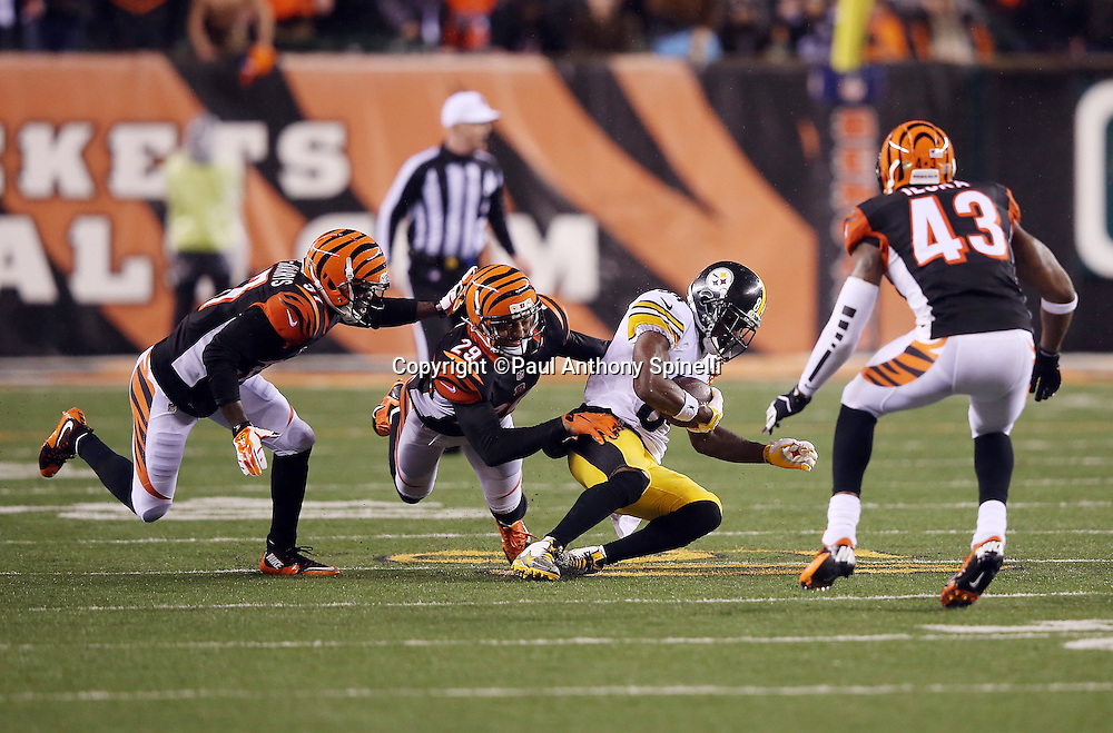 Pittsburgh Steelers wide receiver Antonio Brown (84) looks for running room after catching a pass good for a 12 yard gain and a critical first down at the Cincinnati Bengals 47 yard line with 22 seconds left in the fourth quarter as he is tackled by Cincinnati Bengals cornerback Chris Lewis-Harris (37), Cincinnati Bengals cornerback Leon Hall (29), and Cincinnati Bengals strong safety George Iloka (43) during the NFL AFC Wild Card playoff football game against the Cincinnati Bengals on Saturday, Jan. 9, 2016 in Cincinnati. The Steelers won the game 18-16. (©Paul Anthony Spinelli)