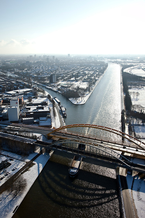 Nederland, Utrecht, Lage Weide, 31-01-2010; spoorbrug en verkeersbrug over het Amsterdam-Rijnkanaal, Hogeweidebrug. Bij de oprit van de brug de fabriek van Douwe Egberts, binnenstad Utrecht aan de horizon;<br /> railway bridge and road bridge over the Amsterdam-Rhine Canal. At the entrance of the bridge the plant Douwe Egberts, Utrecht city on the horizon<br /> luchtfoto (toeslag), aerial photo (additional fee required)<br /> foto/photo Siebe Swart