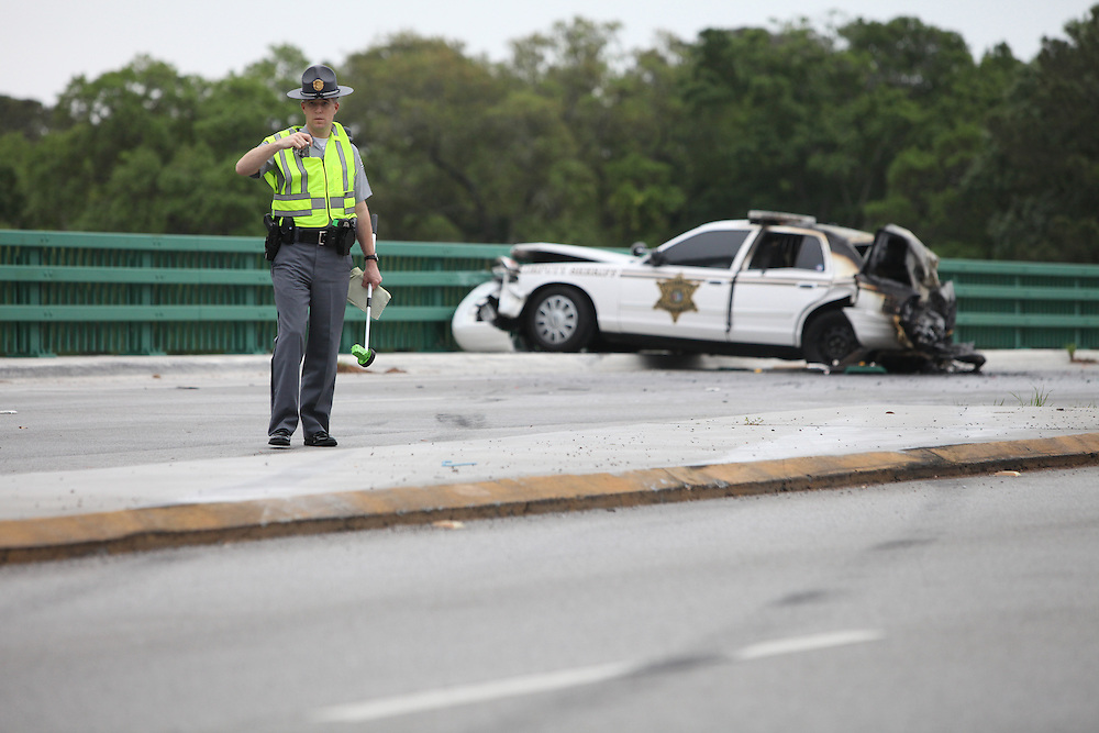 METRO -- Andrew Knapp/STAFF -- A trooper investigates a crash involving an SUV and a Charleston County sheriff's cruiser Tuesday morning on Folly Road at the Ellis Creek Bridge. The wreck closed Folly Road during rush hour.