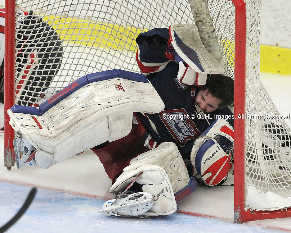 GEORGETOWN, ON  - APR 1,  2017: Ontario Junior Hockey League, South West Conference Championship game between Georgetown Raiders and the Oakville Blades. Brendan McGlynn #34 of the Oakville Blades helmets gets knocked off with the collision as his head makes contact with the centre post during the third period. McGlynn would stay in the game after being assessed by the Team Medical Staff.<br /> (Photo by Tim Bates / OJHL Images)
