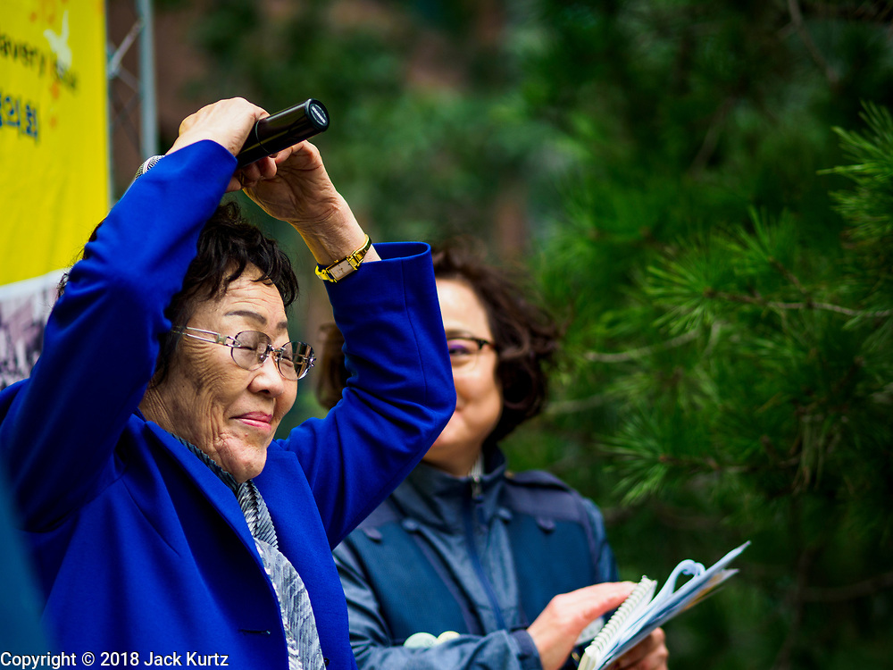 "10 OCTOBER 2018 - SEOUL, SOUTH KOREA: LEE YONG-SOO, one of the few surviving ""comfort women"" weeps and makes a heart symbol with her hands while ending a speech about her experiences as a sexual slave for the Japanese Army during World War II. She was speaking at the Wednesday Demonstration to protest Japan's sexual enslavement of Korean women during World War II. Lee has said she was tortured with electic shock and raped by Japanese soldiers four to five times a day during her enslavement. The Wednesday protests have been taking place since January 1992. Protesters want the Japanese government to apologize for the forced sexual enslavement of up to 400,000 Asian women during World War II. The women, euphemistically called ""Comfort Women"" were drawn from territories Japan conquered during the war and many came from Korea, which was a Japanese colony in the years before and during the war. The ""comfort women"" issue is still a source of anger of many people in northeast Asian areas like South Korea, Manchuria and some parts of China.       PHOTO BY JACK KURTZ   <br /> Wednesday Demonstration demanding Japan to redress the Comfort Women problems"