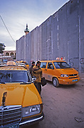 Israeli separation wall divides town of Abis du from sister town. Taxis transport Palestinians around the wall.