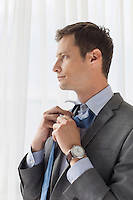 Thoughtful businessman loosening necktie in hotel