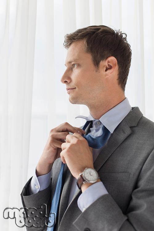 Thoughtful businessman loosening necktie in hotel