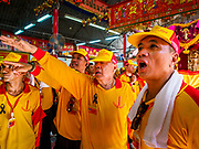 "02 JUNE 2017 - SAMUT SAKHON, THAILAND: The leaders of the team carrying the City Pillar Shrine shout instructions to the team before the procession. The Chaopho Lak Mueang Procession (City Pillar Shrine Procession) is a religious festival that takes place in June in front of city hall in Samut Sakhon. The ""Chaopho Lak Mueang"" is  placed on a fishing boat and taken across the Tha Chin River from Talat Maha Chai to Tha Chalom in the area of Wat Suwannaram and then paraded through the community before returning to the temple in Samut Sakhon. Samut Sakhon is always known by its historic name of Mahachai.      PHOTO BY JACK KURTZ"