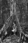 Embera guide Juancito embraces a giant tree along the Rio Sambu, Darien Province, Panama.