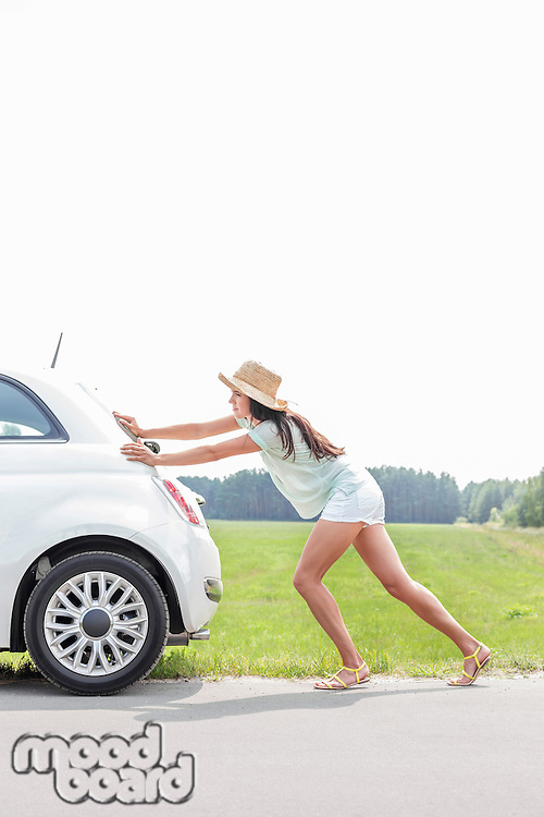 Full-length of woman pushing broken down car on country road