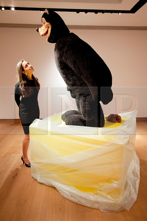 © Licensed to London News Pictures. 05/10/2012. LONDON, UK. A member of Christie's staff examines Paul McCarthys 'Bear Sculpture' (1992) estimated to fetch GB£550,000-750,000 at an auction preview in London today (05/10/12). The evening auction, consisting of post-war and contemporary art, takes place at Christie's St James' auction house on the 11 October 2012. Photo credit: Matt Cetti-Roberts/LNP