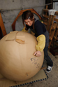 """A worker adds a layer of paper to a """"yonshakudama"""" 420kg firework made by Katakai Fireworks Co., Ltd, Katakai, Japan, April 6, 2009. The company makes the world's largest firework, a 120cm round shell called a """"yonshakudama""""."""