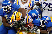 Kentucky football players make a tackle against LSU at Commonwealth Stadium. (Photo by Joe Robbins)