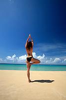 September 2008: Model Sandra Tenuto does morning yoga on the beach on St. Thomas US Virgin Islands beach scenes.  Stock photos available.