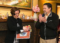 Laconia Planning Director Shanna Saunders receives a gift brick from Mayor Ed Engler that will be inscribed with her name and placed in the WOW Trail Park during a gathering in her honor at the Holy Grail Tuesday evening.  (Karen Bobotas/for the Laconia Daily Sun)