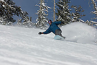 Young man snowboarding at Kirkwood ski resort near Lake Tahoe, CA.