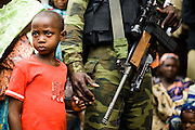 A boy holds the hand of a government solider in the town of Bazzama, Cameroon on Wednesday September 16, 2009.