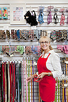 Portrait of senior owner of pet shop showing belt