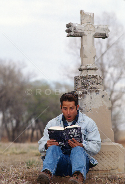 Young man sitting beside a grave marker reading a horror story