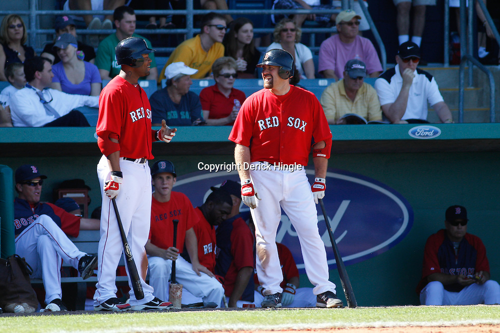 March 7, 2011; Fort Myers, FL, USA; Boston Red Sox left fielder Carl Crawford (13) and third baseman Kevin Youkilis (20) talk before batting during a spring training exhibition game against the Baltimore Orioles at City of Palms Park.   Mandatory Credit: Derick E. Hingle
