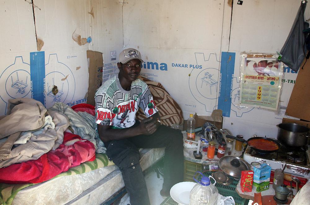 """EUROPE - SPAIN - EL EJIDO ; Illegal Immigration - VEGETABLE & FRUIT Production in Andalusia ; EL PLASTICO ; Exploitation of African workers;.The fruits and vegetables grown in the area are worth about $1.8 billion a year. Most of the workers are Moroccans, often called """"Moros"""" in reference to the Moors who ruled southern Spain for 700 years; Europa - SPANIEN - Landwirtschaft.Die Region um El Ejido, Provinz Almeria in Andalusien, gilt als Europas  größter agrarindustriell genutzter """"Wintergarten"""". Unter ca. 36.000 Hektar Plastik (Treibhäusern) wird ganzjährig Obst und Gemüse angebaut, welches zum Großteil in Supermärkten in Nordeuropa, Deutschland und England verkauft wird... Unter den Plastikplanen werden ca. 60.000, meist illegale Einwanderer aus Marokko, Schwarzafrika, Osteuropa beschäftigt. Arbeitsschutz und Mindestlöhne werden nicht eingehalten. .HIER: Mohamed, 25, aus dem Senegal in seiner Behausung, tagsüber ohne Job;  Die meisten der papierlosen Migranten leben in so genannten Chabolas, Hütten aus notdürftig zusammengezimmerten Paletten und Plastikplanen. Tagsüber arbeiten sie als Tagelöhner in den Gewächshäusern, abends kehren sie in ihre Behausungen zurück, wo es weder sanitäre Anlagen, noch fließendes Wasser oder Elektrizität gibt. Südlich von El Ejido....23.03.2007.Copyright: Christian Jungeblodt"""