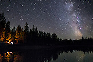 The milky way is reflected over Kreis Pond in Montana as a campfire burns on the left. In October, the brightest part of the galaxy is only visible in the early evening before it sets for the night.