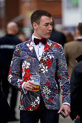 LIVERPOOL, ENGLAND - Thursday, April 6, 2017: A male race goer dressed in a flower patter jacket and red velvet bow tie, during The Opening Day on Day One of the Aintree Grand National Festival 2017 at Aintree Racecourse. (Pic by David Rawcliffe/Propaganda)