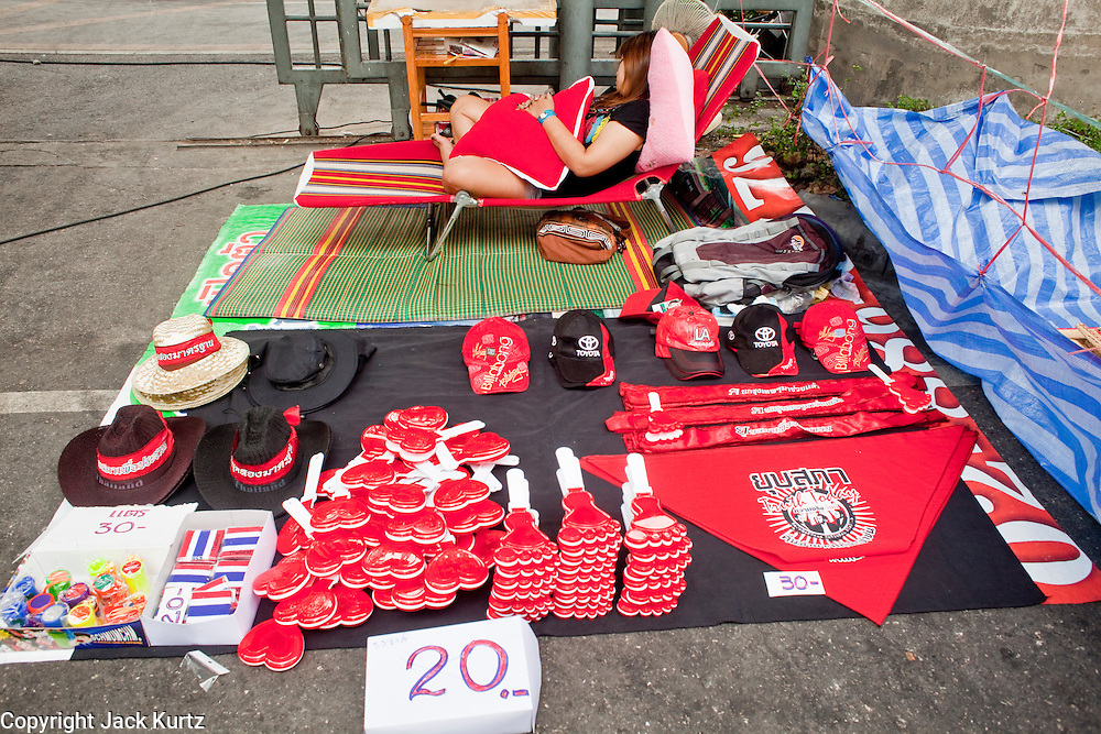 18 APRIL 2010 -- BANGKOK, THAILAND: A Red Shirt souvenir vendor sleeps while she waits for business. The Red Shirts protest in the Ratchaprasong Shopping district, home to Bangkok's most upscale malls, is costing the Thai economy millions of Baht per day because the malls and most of the restaurants are closed and tourists are staying away from the area. But that hasn't stopped the Red Shirts who have brought their own economy with them. There are Red Shirt restaurants, food stands, souvenir vendors and more, creating a micro economy for Red Shirts in the area.  The Red Shirts continue to occupy Ratchaprasong Intersection an the high end shopping district of Bangkok. They are calling for Thai Prime Minister Abhisit Vejjajiva to step down and dissolve the parliament. Most of the Red Shirts support ousted former Prime Minister Thaksin Shinawatra.   PHOTO BY JACK KURTZ