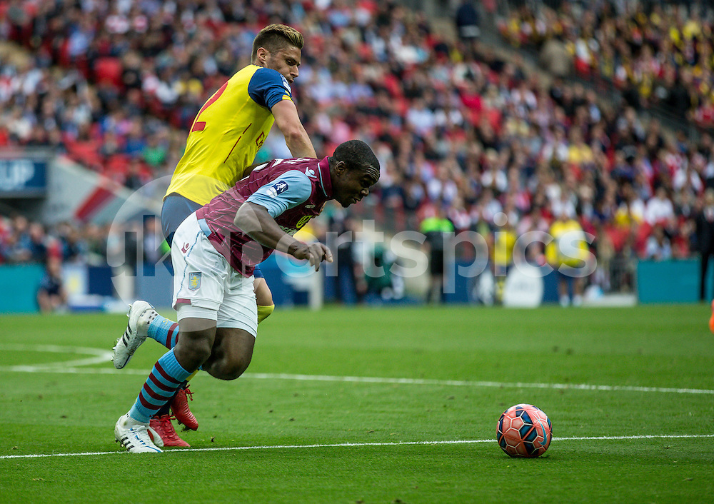 Jores Okore of Aston Villa tries to get away from Oliver Giroud of Arsenal during the The FA Cup Final match between Arsenal and Aston Villa at Wembley Stadium, London, England on 30 May 2015. Photo by Liam McAvoy.