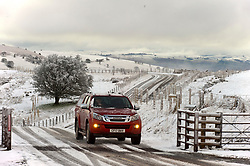 © Licensed to London News Pictures. 27/02/2020.  Builth Wells, Powys, Wales, UK. A farmer drives  through a wintry landscape on the Mynydd Epynt moorland along the B4520 (Brecon road) between Builth Wells and Brecon after snow fell on high land last night in Powys, Wales, UK. Photo credit: Graham M. Lawrence/LNP