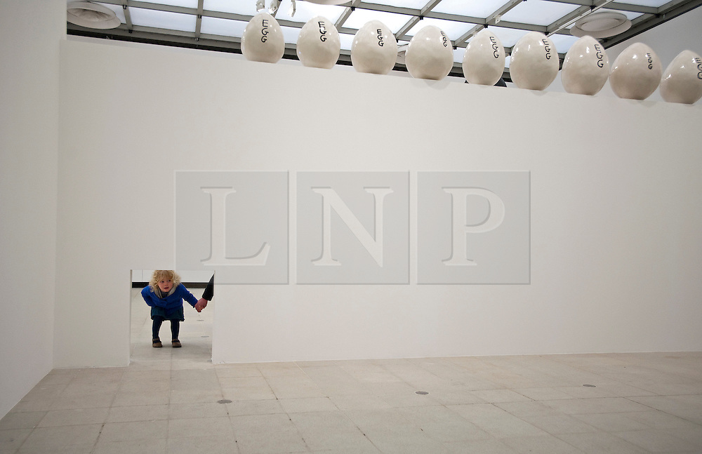 © London News PIctures. 31/01/2012. A small girl peeking through a hole in front of artwork titled '12 Large Eggs (2011)' at a press viewing of exhibition 'Brain Activity, by British artist David Shrigley at the Hayward Gallery, London on January 31st, 2012. Photo credit: Ben Cawthra/LNP