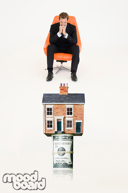 House on top of roll of bills with pensive businessman on chair representing expensive real estate