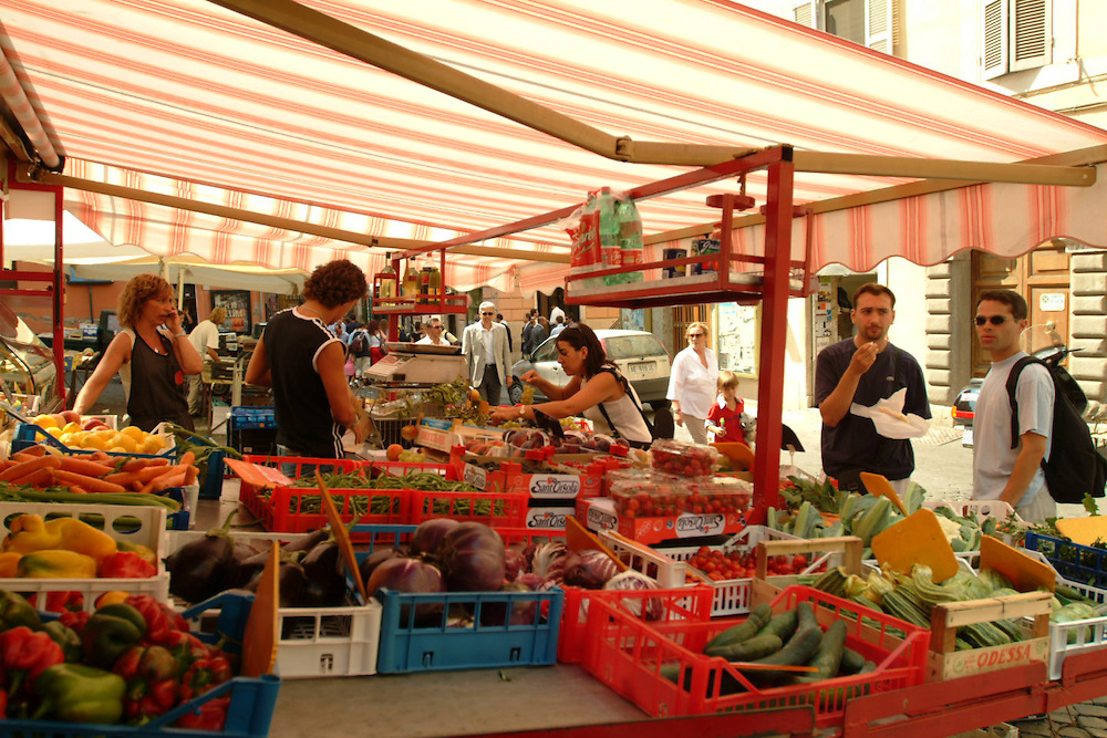 Vendors and customers in street market in Rome, Italy