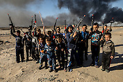 Children learn young about guns in Iraq and these boys joked that they were the ones that drove ISIS out of their town. In a few years many of them will be holding the real thing. Qayyara, Iraq. Nov. 23, 2016. (Photo by Gabriel Romero ©2016)